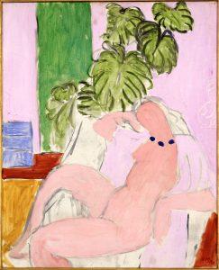 Nudo in poltrona, pianta verde
