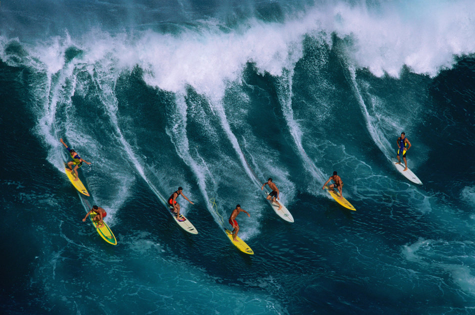 Seven surfers riding large wave, Hawaii, USA, aerial view