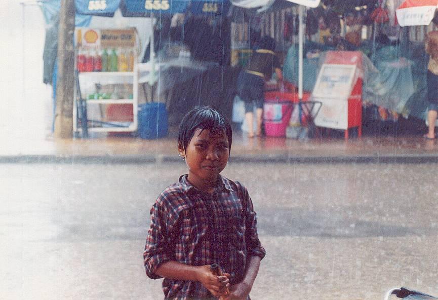 Bambino sotto la pioggia in Cambogia