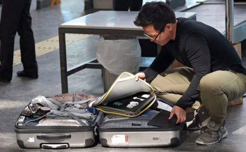 Un passeggero apre la valigia e protegge alcuni dispositivi elettronici nell'aeroporto di Turchia