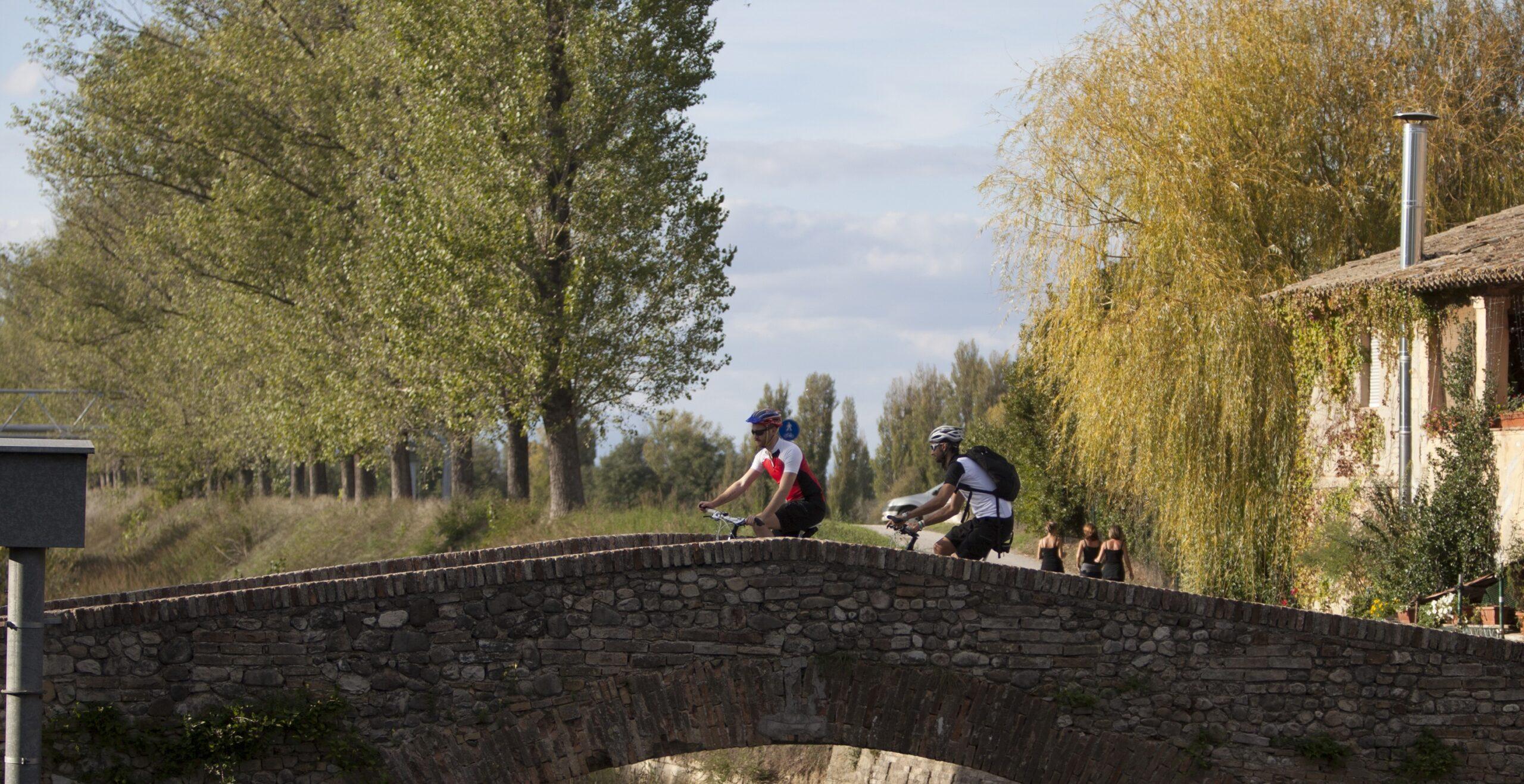 Ponte di pietra con ciclisti lungo la ciclovia Assisi - Spoleto.