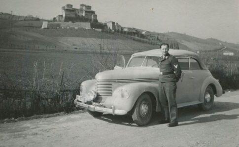 Uomo fuori da un auto con sfondo paesaggistico. Fonte: Direzione Regionale Musei Emilia Romagna. Paesaggi culturali