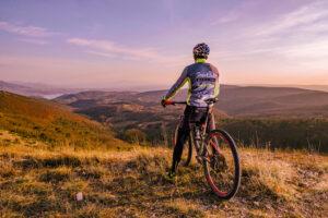 Parco naturale, Umbria. CIclista sul Monte Peglia osserva il tramonto. Via Umbria Tourism..