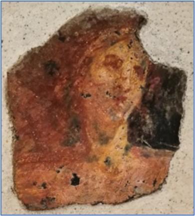 Frammento di affresco con parte di figura femminile su fondo nero con corona di foglie di alloro. Probabile pertinenza all'area stabiana per stretto confronto con una figura femminile con lira presente nell'affresco di Hermes, da Villa San Marco (in esposizione al Museo Libero D'Orsi, inv. 62526).